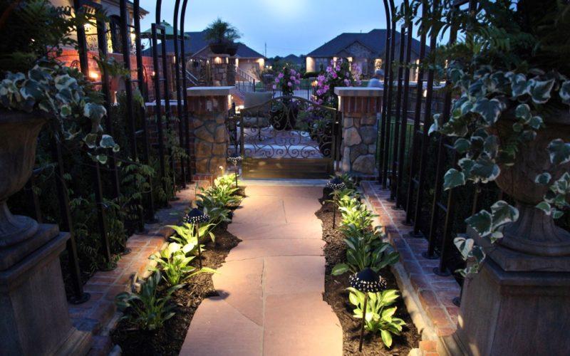 Landscaped path to ornamental iron gate.
