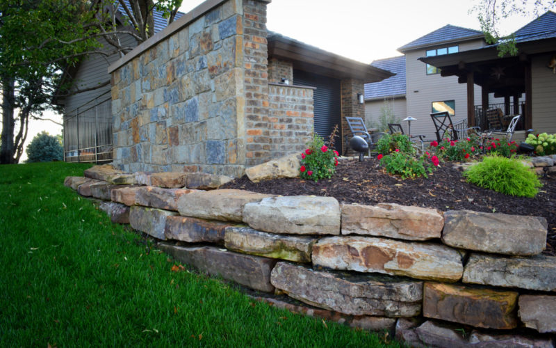 Moss rock retaining wall and outdoor kitchen